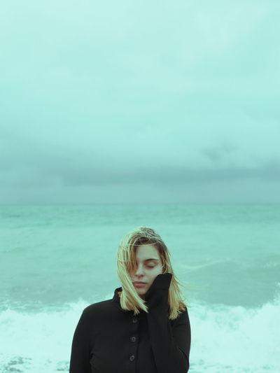 Portrait of mature man standing against sea