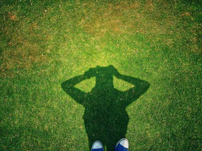 Shadow Of Man Standing On Grassy Field