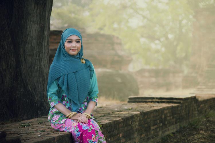 Beautiful woman wearing hijab sitting on retaining wall