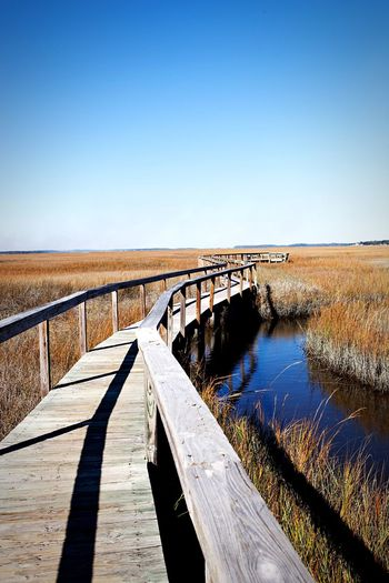 Pier over water amidst dry grass against clear sky
