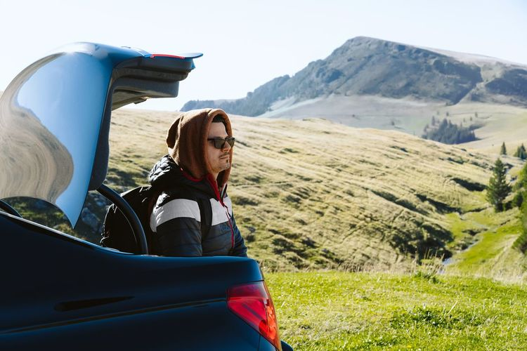 Portrait of young man on car land at mountain