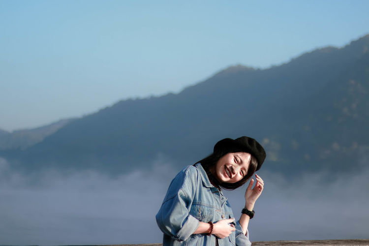 Portrait of smiling woman standing by railing against mountains
