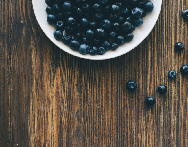 Directly Above Shot Of Blueberries In Plate On Wooden Table