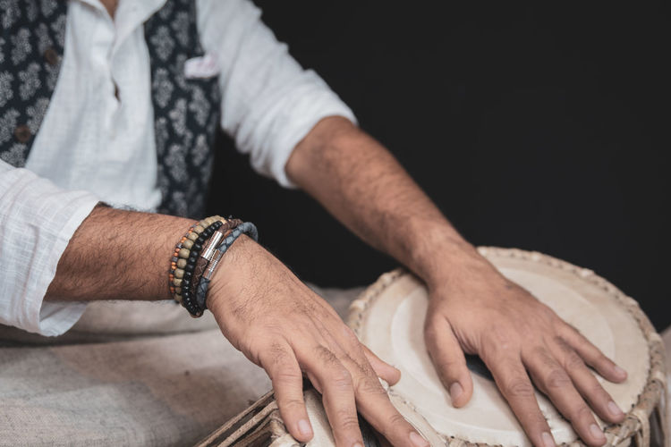 Midsection of man playing tabla against black background