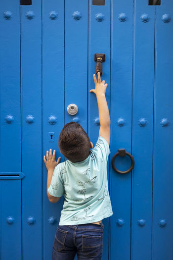 Boy standing against blue door