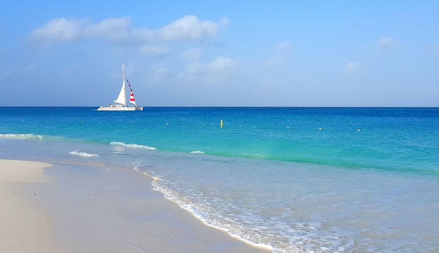 Calm Sailing Serenity Water And Sky Beach Beauty In Nature Calm Seas Day Flag Horizon Over Water Landscape Majestic Nature No People Outdoors Painterly Effect Sailboat Sand Scenics Sea Sky Tranquil Scene Tranquility Vacaton Water Water And Horizon