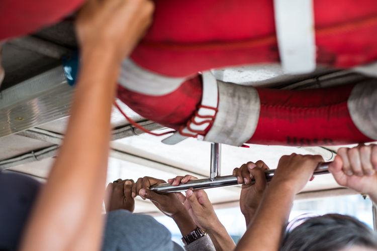Cropped Hand Of People Holding Metal Rod In Ferry