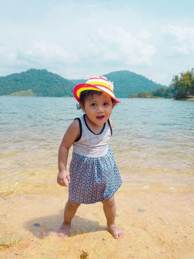Portrait of cute boy standing at beach