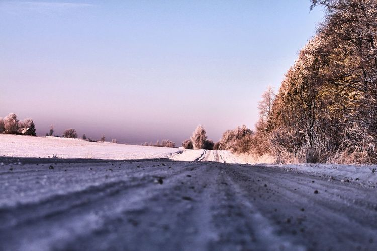 Snow covered street during winter against clear sky