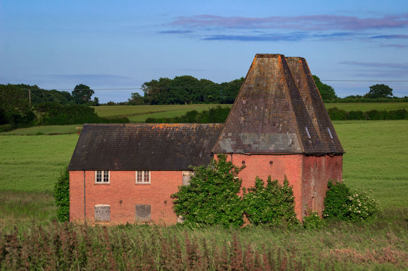 Oast House, Garden Of England , Kent, England. No People Day Architecture Vivid International Hops Beer Drying Process Rural Scene Countryside Travel Destinations Tourism Getty Images EyeEm Gallery Built Structure Plant Sky Building Exterior Field Land Nature Building House Landscape Tree Old Grass Green Color History The Past Scenics - Nature Outdoors Cottage