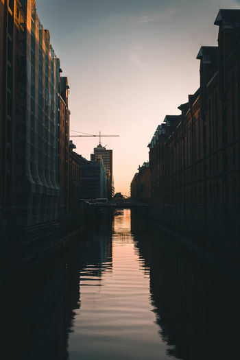 Canal amidst buildings against sky during sunset