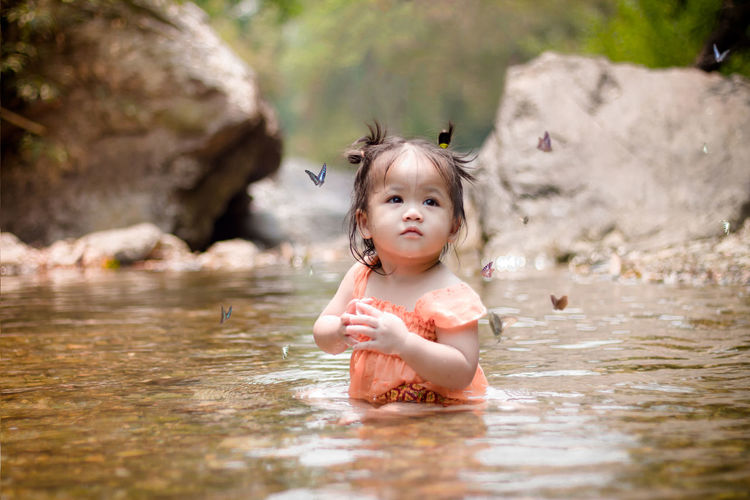baby cute girl playing water in the river with butterfly Childhood Water Child Portrait Innocence Cute One Person Baby Young Looking At Camera Front View Real People Babyhood Selective Focus Waterfront Day Outdoors Girl Buterfly Daughter River Girl, Little, Outdoor, Beautiful, Nature, Happy, Summer, Portrait, Caucasian, Cute, Water, Spring, Umbrella, Boots, Raincoat, Grass, Child, Small, Kid, Play, Childhood, Outside, Baby, Playful, Butterfly