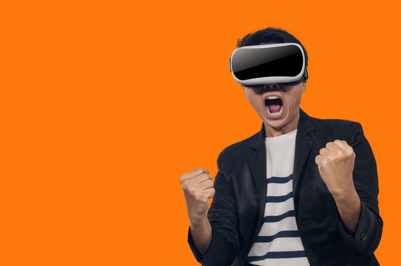 Young man with a virtual reality headset stand on orange background indoor. Virtual Reality Headset Man Vr Glasses Young Technology 3D Entertainment Male Device White Modern Isolated Fun Game person Background Futuristic Video Using Playing Happy Concept Gaming Leisure Lifestyle People Guy Mask Looking Equipment Future Gamer Wearable Touching Excited