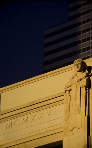 Low angle view of statue against building in city