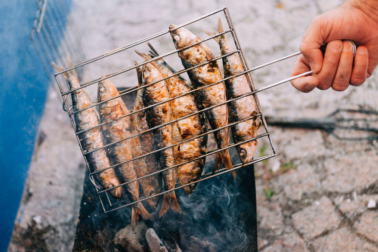 Cropped Image Of Hand Grilling Fish On Barbecue