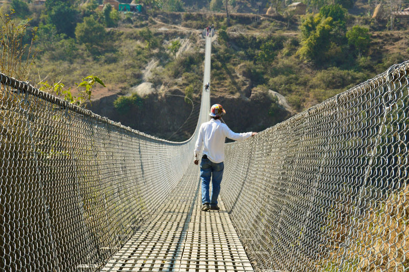 Rear View Young Man On Rope Bridge