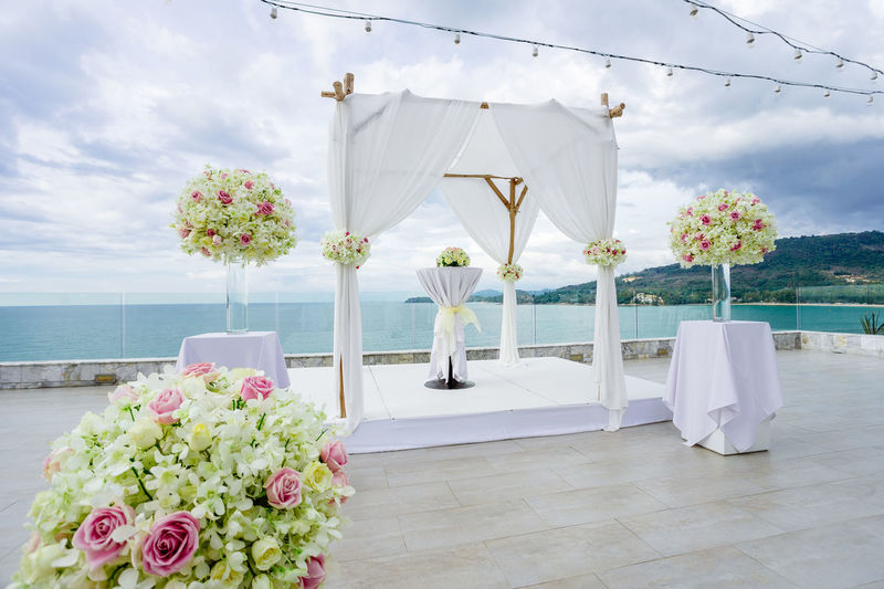Wedding venue setup for ceremony with the panoramic ocean and island view in background. Wedding arch, altar decoration with roses, flowers, floral Altar Architecture Banquet Celebration Gazebo Setup Venue Wedding Aisle Beach Bouquet Ceremony Decoration Floral Flowers Hill Island Ocean Preparation  Roses Samui Scenics Seascape Sky Tropical