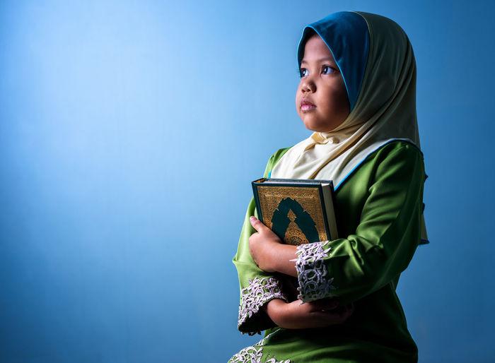 Girl wearing hijab holding koran while sitting against blue background
