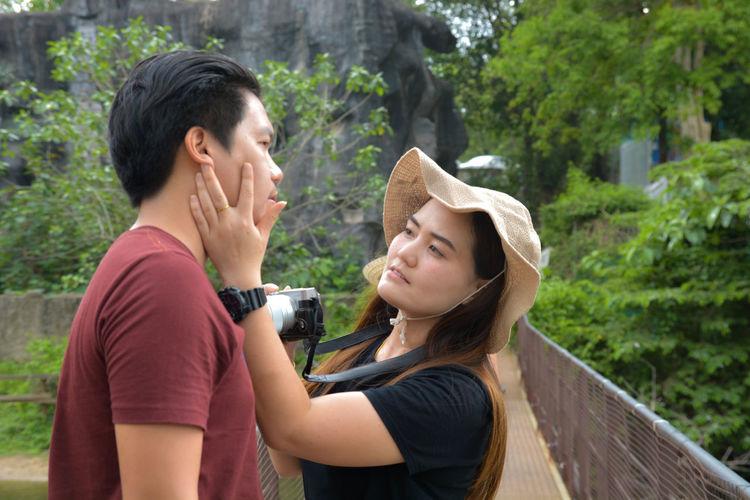 Woman touching man cheek while standing on footbridge