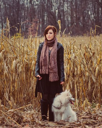 Full Length Portrait Of Beautiful Woman With Dog Standing On Dry Corn Field During Winter