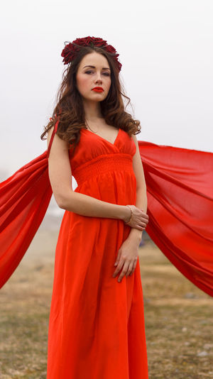 Portrait of woman in red dress standing against sky