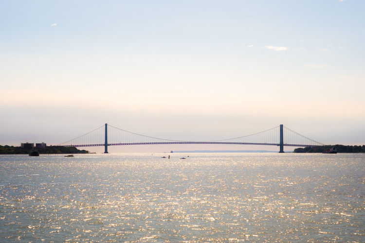 Distant view of verrazano-narrows bridge over bay against sky