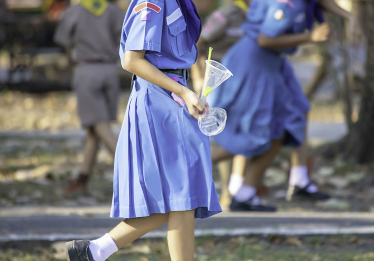 Midsection of schoolgirl holding disposable containers on footpath