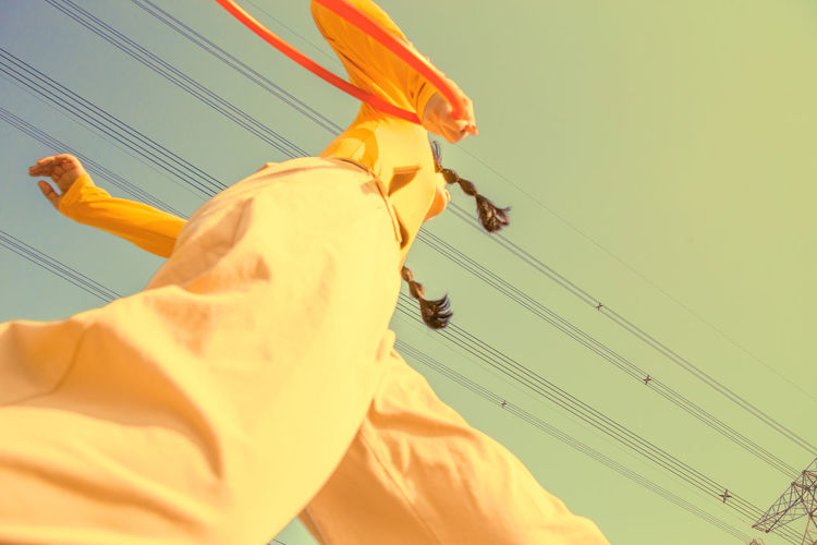 Low angle view of woman against cables and clear sky