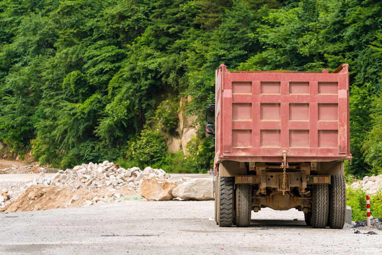 On the highway truck Construction Heavy Industrial Logistics Road Bulky Car Wheels Cargo Container Close-up Construction Engineeeee Dense Dirt Dusk Engineering Freight Transportation Good Highways Land Transportation Loading Material Mine Mineral Of Traffic Transportttttt On The Road Outdoors