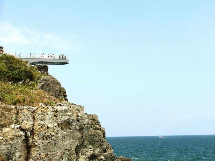 Low Angle View Of People At Observation Point Over Cliff In Sea Against Sky