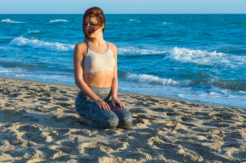 Full Length Of Young Woman Exercising On Sand At Beach