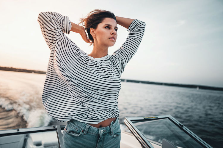 Water Striped One Person Three Quarter Length Casual Clothing Young Adult Lifestyles Leisure Activity Standing Real People Adult Nautical Vessel Day Transportation Women Sea Young Women Outdoors