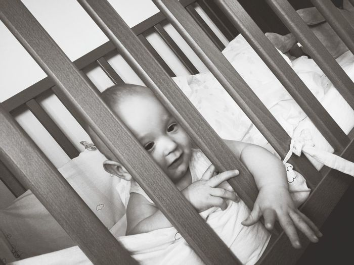 Close-up of baby boy looking through railing while lying in crib