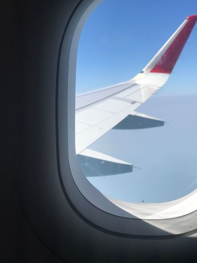 Airplane flying in sky seen through glass window