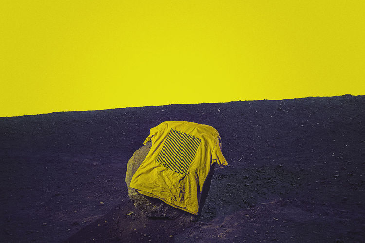 Yellow umbrella on land against clear sky