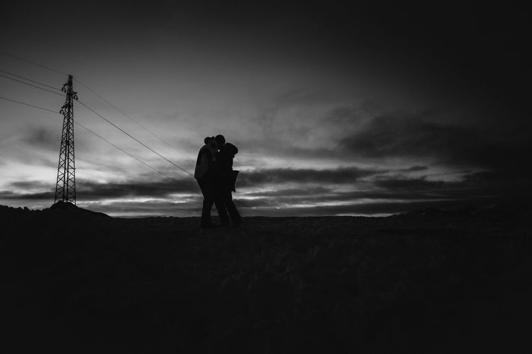 Silhouette Couple On Field At Dusk