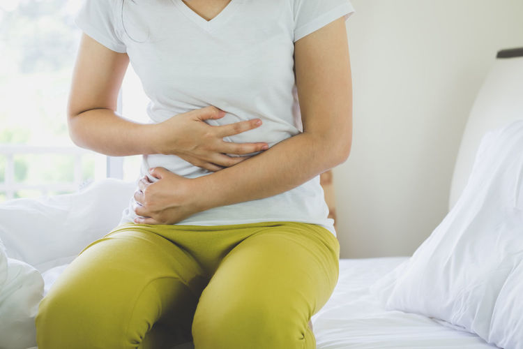 Midsection of woman with stomachache kneeling on bed at home