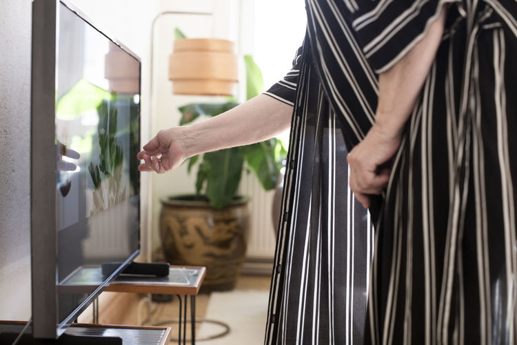 Midsection of woman holding glass while standing at home