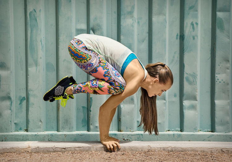 Side View Full Length Of Woman Exercising Against Wall