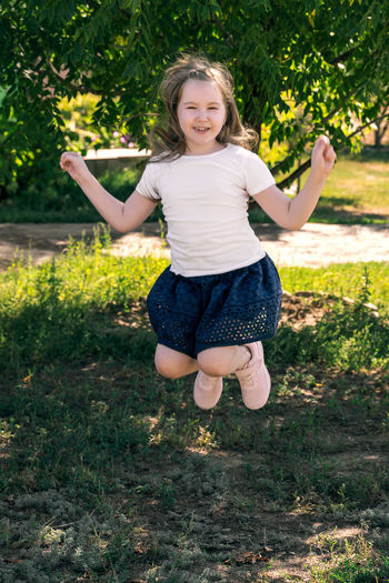 Cute smiling little girl in white t-shirt and dark blue skirt jump outdor in field.