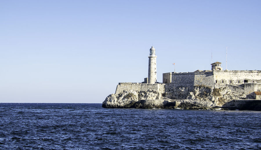 Morro castle by sea against clear sky