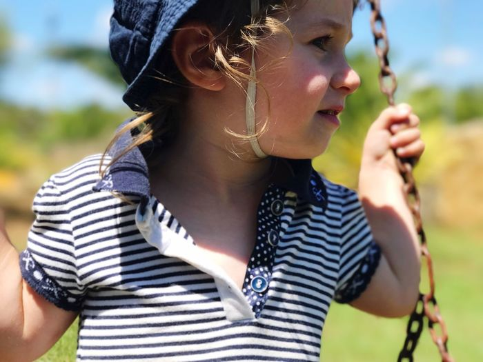Close-up of cute girl sitting on swing while looking away