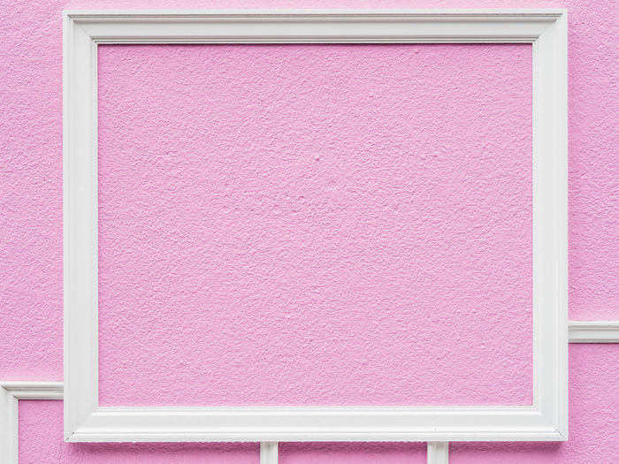Close-up of pink paper against wall
