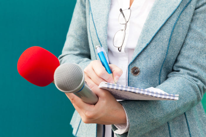 Female reporter at work, taking notes and holding two microphones. Communications Information Overload Journalist Mic PR Press Reporting Writing Blue Background Broadcasting Journalism Correspondent Female Reporter Information Journalism Media Microphone Microphones News News Event Notebook Notes Pencil Press Conference Public Speech Reporter