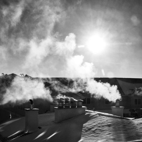 Smoke Emitting From Houses Against Sky During Winter