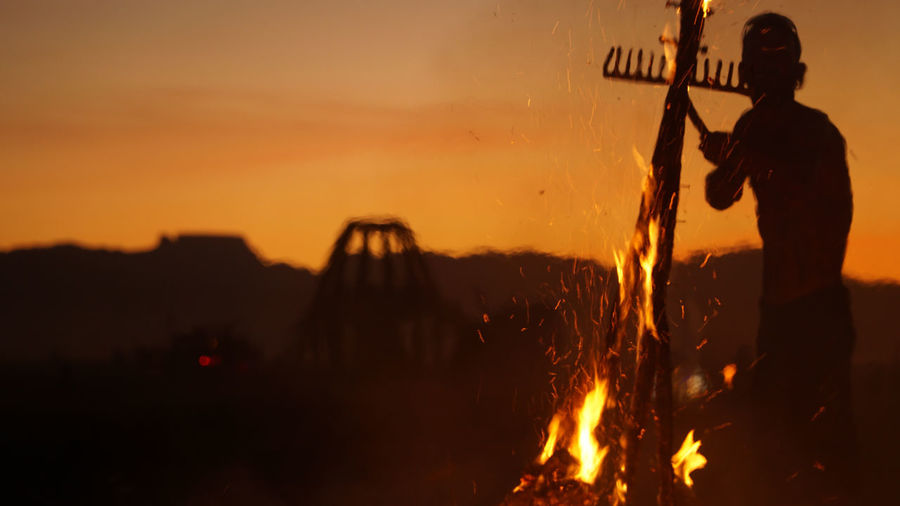 Silhouette man standing by bonfire against sky during sunset