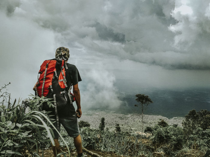 Rear view of hiker standing while looking at cloudy sky