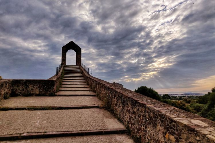 Staircase by footpath against sky during sunset