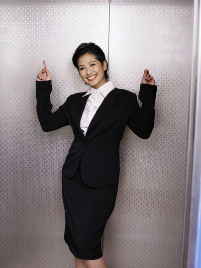 Portrait of smiling businesswoman gesturing in elevator