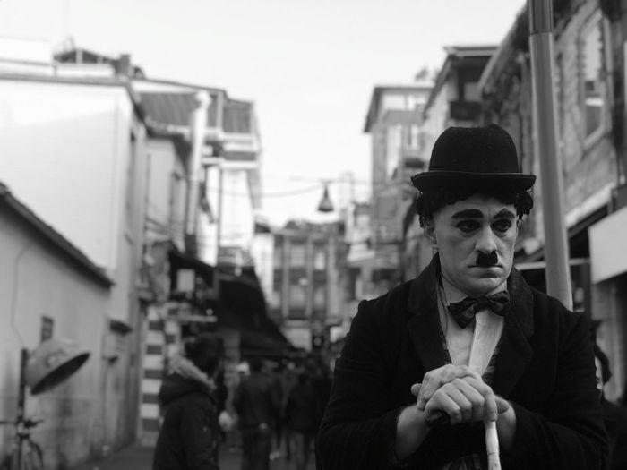 Man imitating charlie chaplin standing on street